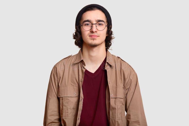 La photo de l'adolescent masculin bouclé porte les lunettes optiques de rond, chapeau noir, chemise occasionnelle, regarde direct photographie stock