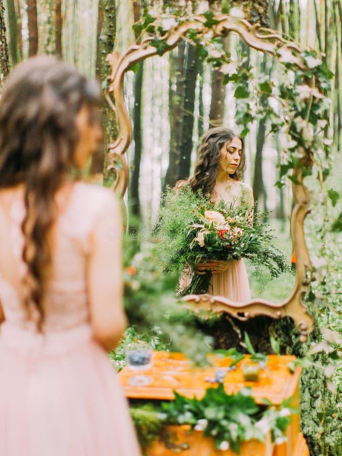 La photo de la femme avec de longs cheveux bouclés et bouquet coloré énorme regardant le côté droit et son ferlection dedans photographie stock