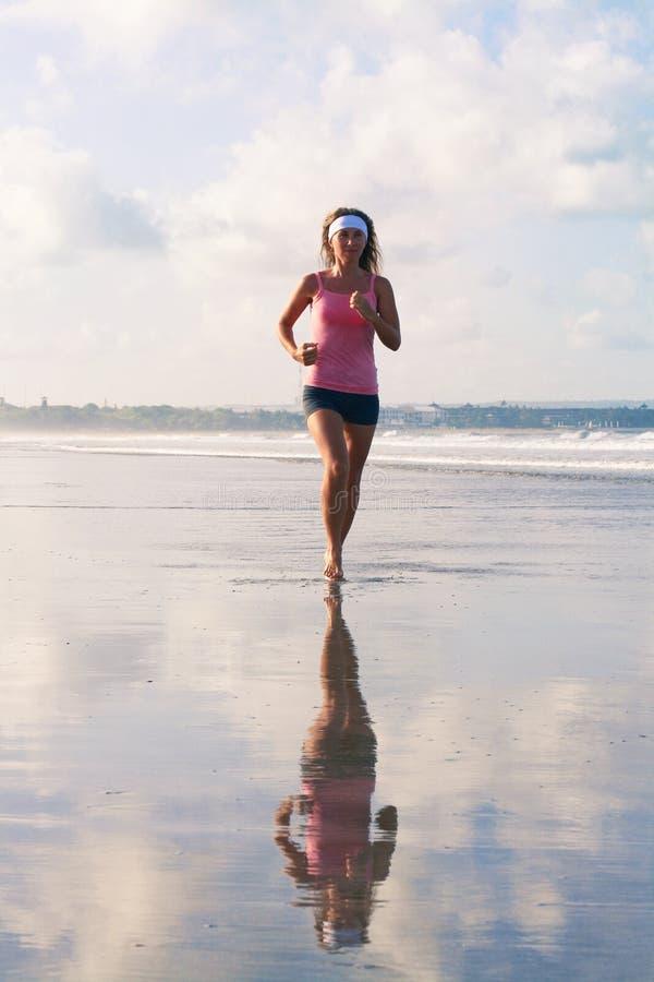 La photo de la fille de sports fonctionne le long de la plage photos libres de droits