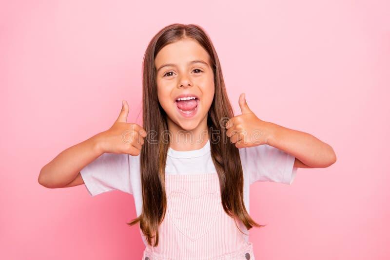 La photo de plan rapproché des cheveux bruns de petite dame donnent à la marque experte de grands jouets que les pouces portent l photos libres de droits