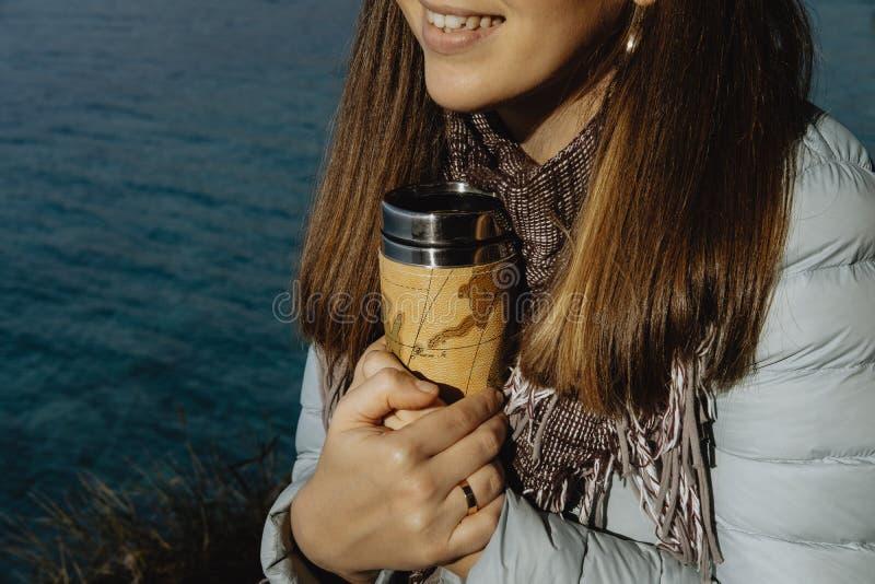 La photo de plan rapproché de la jeune femme dans le manteau bleu tient un thermos avec h photo stock