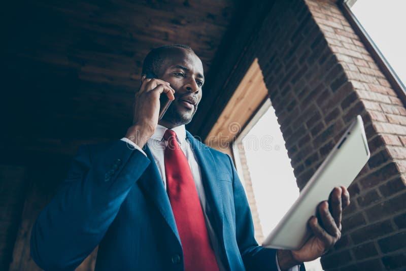 La photo de vue d'angle faible de la main foncée de téléphone de participation de type de peau discutant le contrat a observé dan image libre de droits