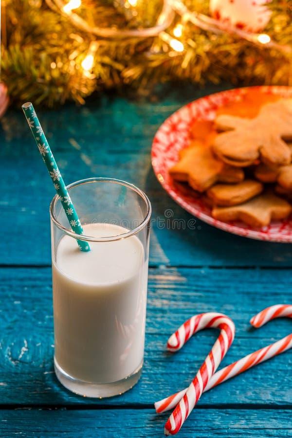 La photo des biscuits de gingembre, verre de lait, caramel colle, les branches impeccables avec la guirlande brûlante photo stock