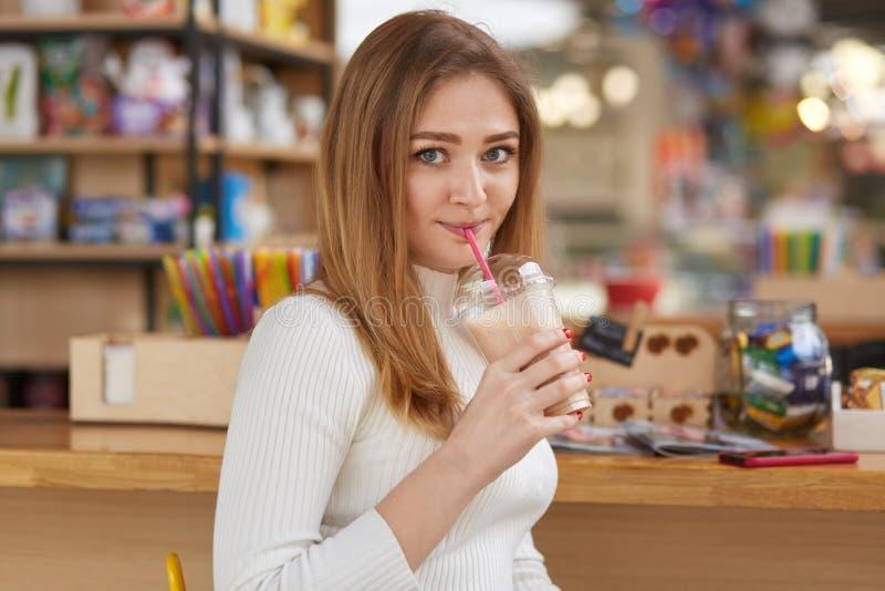 La photo des boissons femelles attrayantes traient le cocktail avec la paille, poses dans la barre, porte le pullover blanc, rega image stock