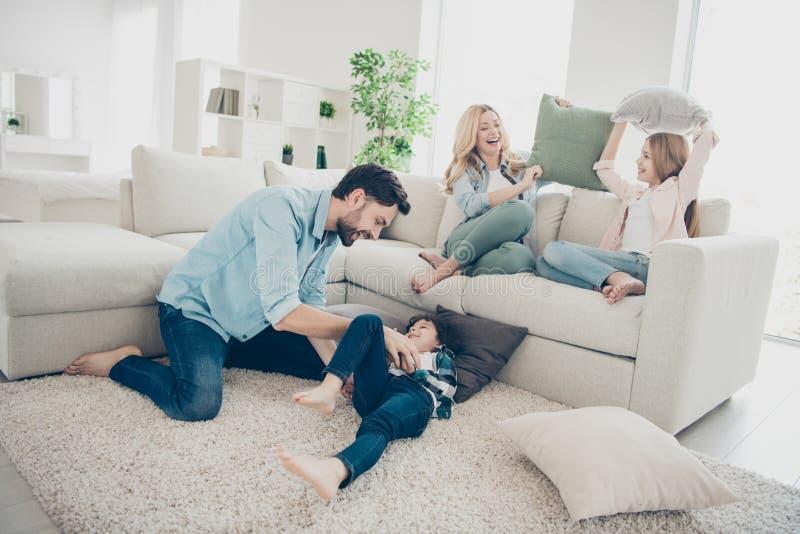 La photo des membres adoptés de la famille quatre dépensent le rire bébête de combat d'oreillers de temps libre reposent le salon photo stock