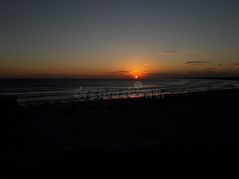 La photo du coucher du soleil d'été dans Arraial font Cabo - fin de l'après-midi avec des personnes sur le sable de plage photos libres de droits