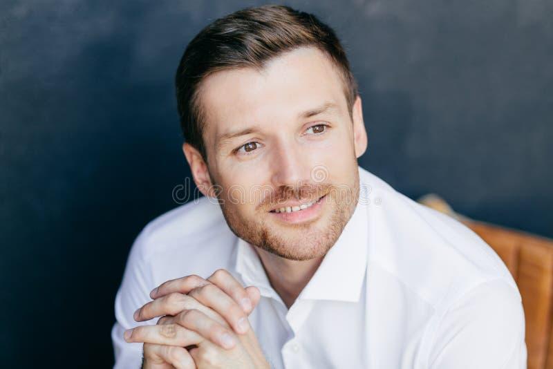 La photo du jeune mâle songeur gai avec le poil, rêves au sujet de quelque chose agréable, utilise la chemise blanche, pose contr images stock