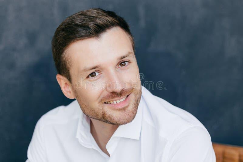 La photo du mâle non rasé beau avec le poil habillé dans la chemise blanche élégante, a le sourire avec du charme, heureux de ren photo libre de droits