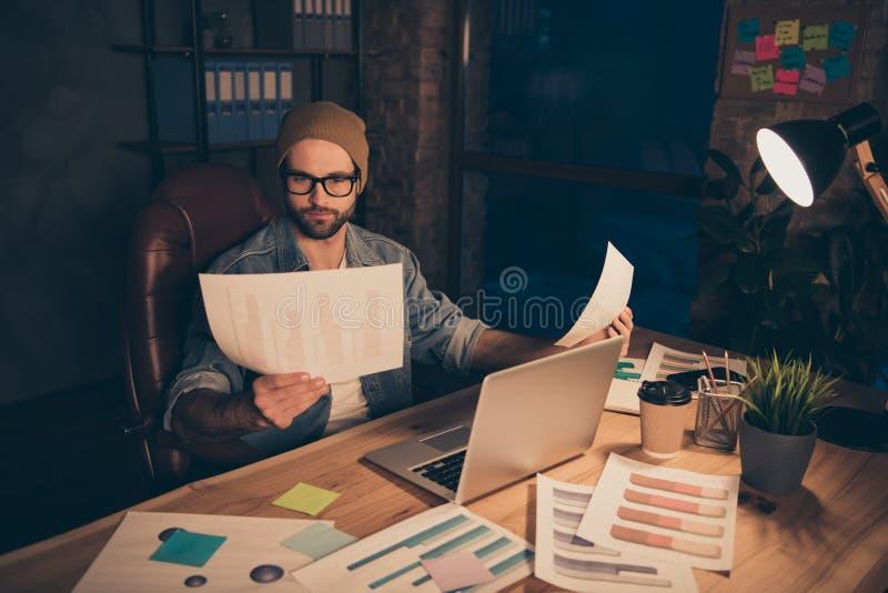 La photo du travail attentif de type au temps de jour sombre lisant des journaux de revenu de finances utilisent l'équipement occ images stock