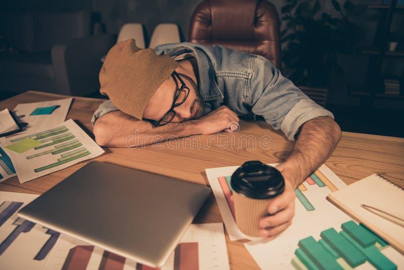 La photo du travail au type foncé de patron de temps est tombée boisson chaude endormie de café n'aidant pas l'équipement occasio photos libres de droits