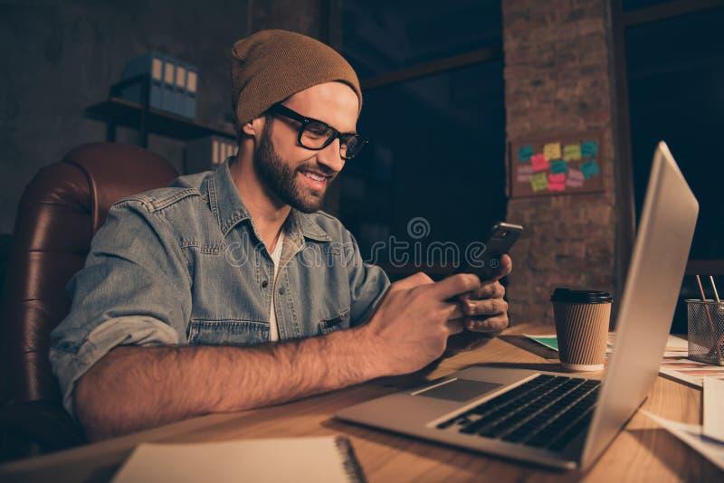 La photo du travail frais de type au temps foncé écrivant des collègues de sms utilisent l'équipement occasionnel pour reposer le images stock
