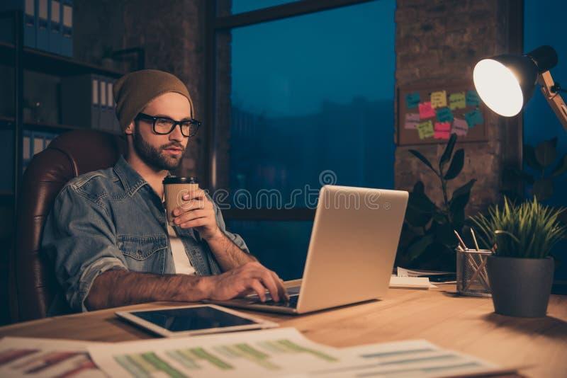 La photo du type sûr travaillant tard la nuit analysant l'email de collègues habillé dans l'équipement occasionnel reposent le bu photographie stock