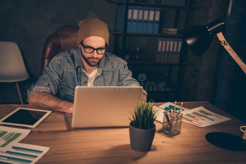La photo du type sûr travaillant tard la nuit analysant l'email de collègues habillé dans l'équipement occasionnel reposent le bu image libre de droits