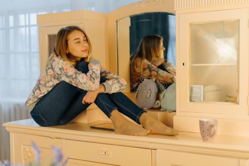 La photo en gros plan horizontale du jeune adolescent rêvant étreignant ses genoux tout en se reposant sur la coiffeuse images stock