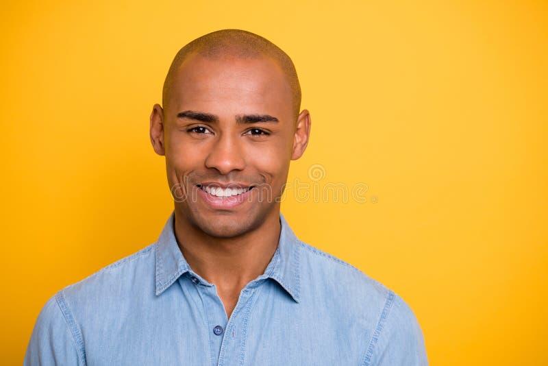 La photo haute étroite de la chemise positive macho de denim de jeans d'usage d'humeur de peau foncée toothy a isolé le fond jaun image stock