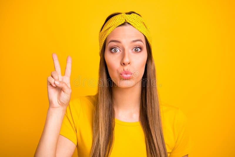 La photo haute étroite de la personne puérile faisant des v-signes avec des lèvres a boudé dodu d'isolement au-dessus du fond jau photos stock