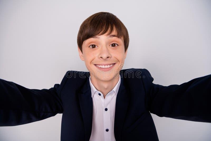 La photo haute étroite du garçon gai positif font détendre le repos de temps libre d'amusement pour faire le blogger de photo que photo stock