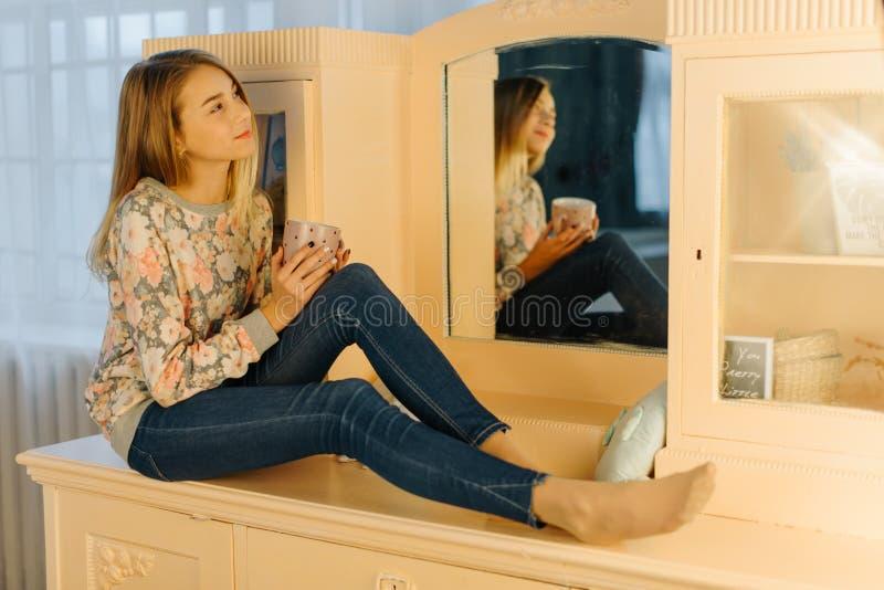 La photo horizontale de la jeune fille rêvante tenant la tasse de thé et s'asseyant sur la coiffeuse image stock