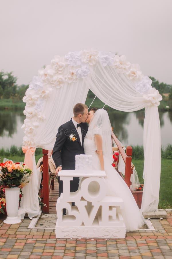 La photo intégrale des nouveaux mariés de baiser derrière le signe et la voûte de mariage photos libres de droits
