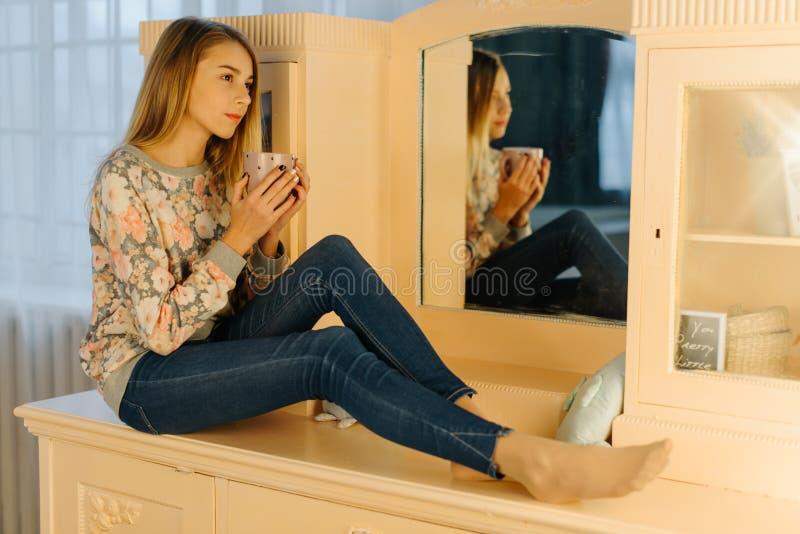 La photo latérale de l'adolescente tenant la tasse de thé tout en se reposant sur la coiffeuse image stock