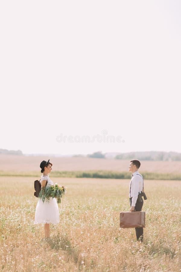 La photo latérale verticale intégrale des nouveaux mariés se tenant loin dans le domaine La jeune mariée tient le coloré image libre de droits