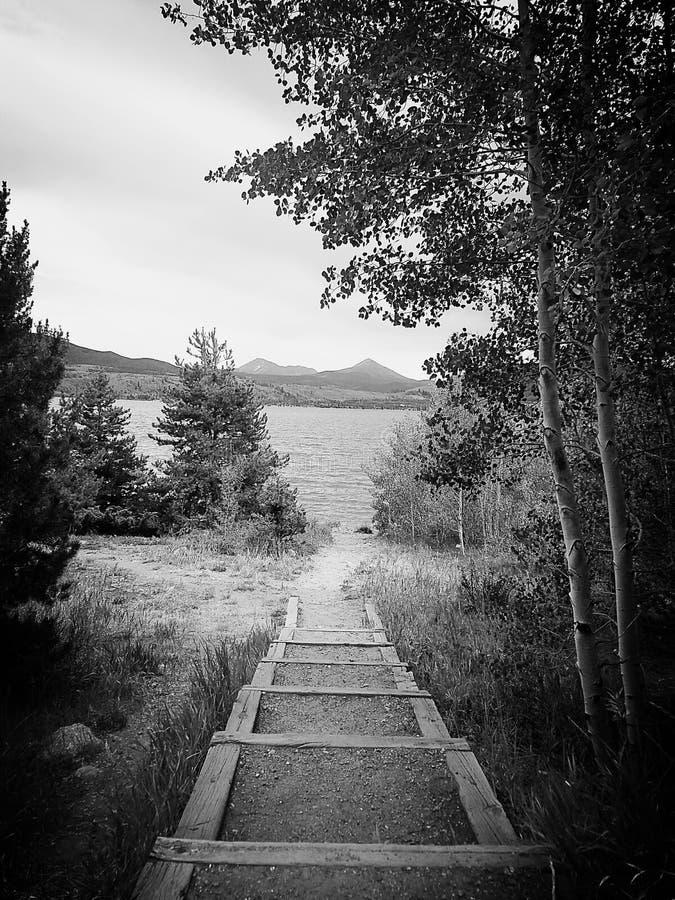 La photo noire et blanche de ramène à un lac photo stock