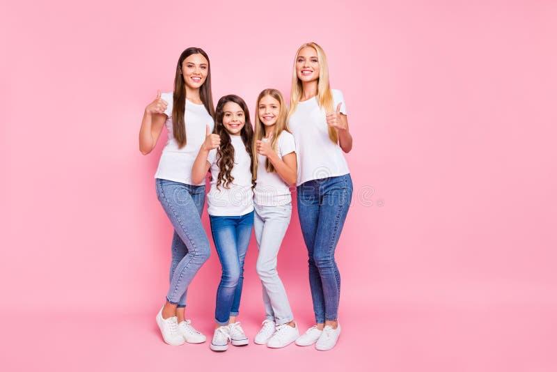 La photo normale de différentes dames d'âge soulevant des pouces portent le fond rose d'isolement par équipement occasionnel photo stock