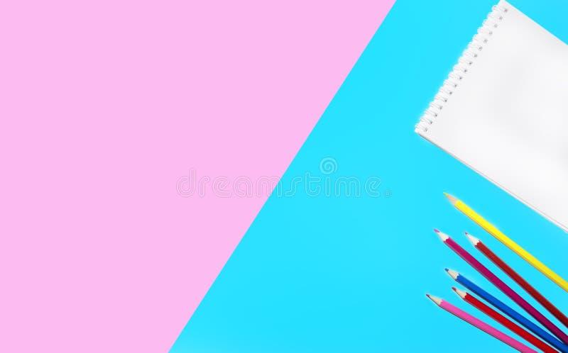 La photo plate de configuration des crayons, du bloc-notes coloré et des ciseaux rayés sur une surface douce a isolé le fond de r photo libre de droits