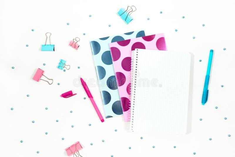 La photo plate de configuration du bureau blanc de bureau avec le comprimé et le carnet bleu rose élégant copient le fond de l'es photos stock