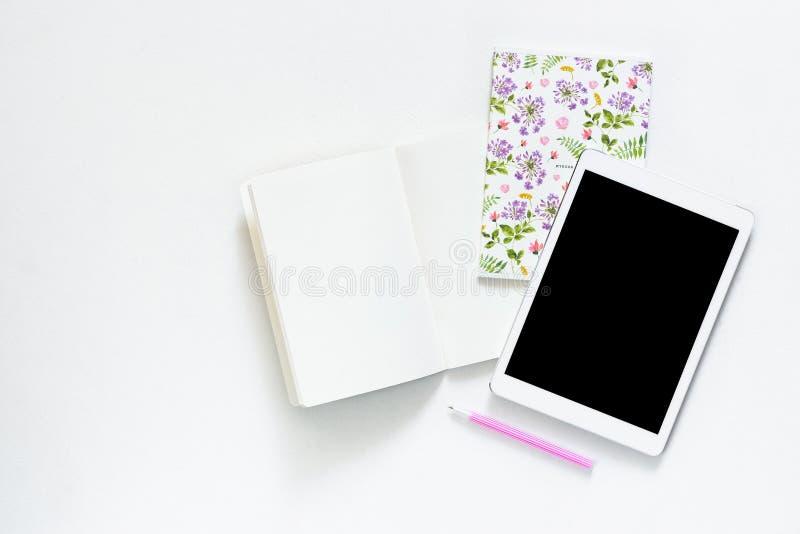 La photo plate de configuration du bureau blanc de bureau avec le comprimé et le carnet ouvert copient le fond de l'espace photographie stock