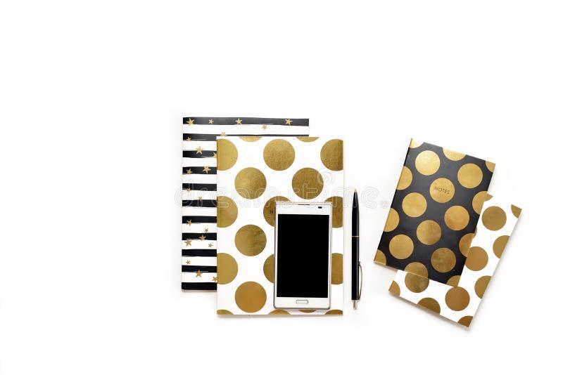 La photo plate de configuration du bureau blanc minimalistic avec le téléphone et les carnets élégants d'or copient le fond de l' images stock