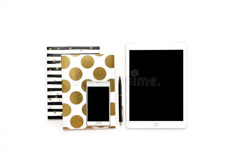 La photo plate de configuration du bureau blanc minimalistic avec le téléphone, le comprimé et les carnets élégants d'or copient  image libre de droits