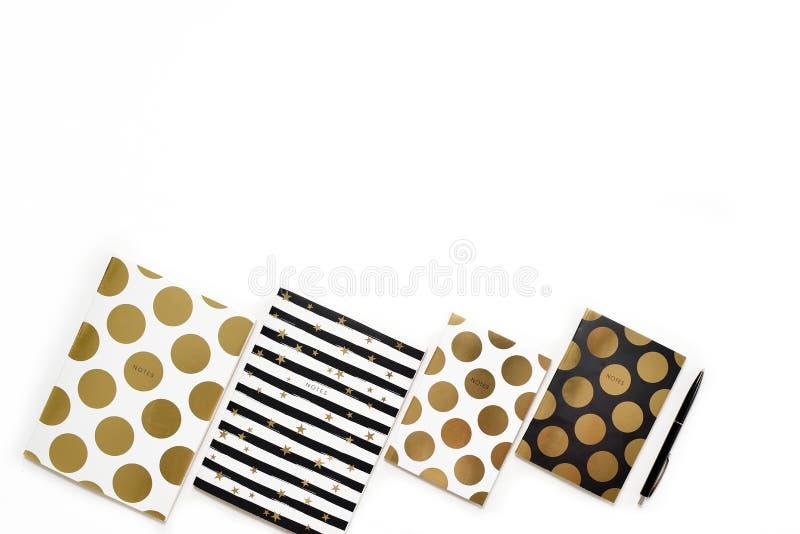 La photo plate de configuration du bureau blanc minimalistic avec les carnets élégants d'or copient le fond de l'espace photographie stock