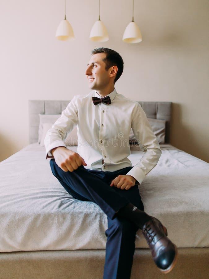 La photo verticale de la jambe se reposante de marié sur la jambe sur le lit tout en regardant par la fenêtre images stock