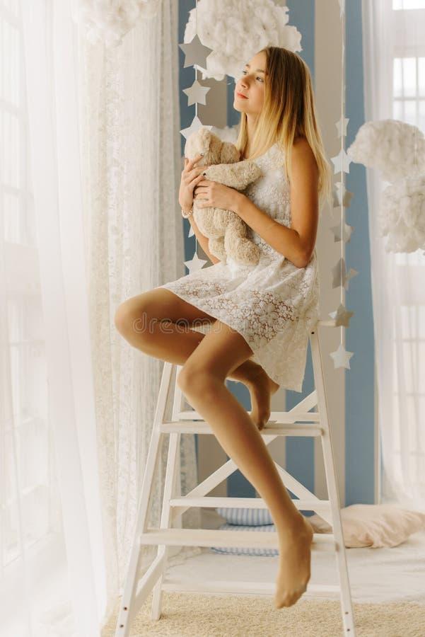 La photo verticale de l'adolescent songeur étreignant l'ours de nounours tout en se reposant sur la chaise et regardant par la fe photo stock