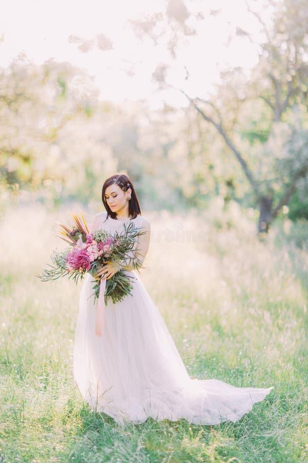 La photo verticale de la belle jeune mariée dans la longue robe, avec des accessoires de cheveux, tenant le grand bouquet des fle photographie stock