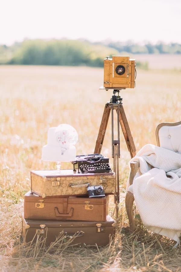 La photo verticale de la pièce du sofa placé à côté des valises de vintage, du vieil appareil-photo et de la machine à écrire au image stock