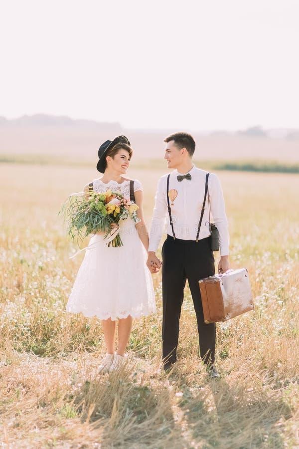 La photo verticale intégrale du vintage a habillé des nouveaux mariés marchant et tenant des mains dans le domaine ensoleillé La  photo stock