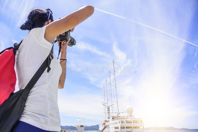 La photographe de jeunes femmes prend à l'appareil-photo sur un fond de ciel bleu photos stock