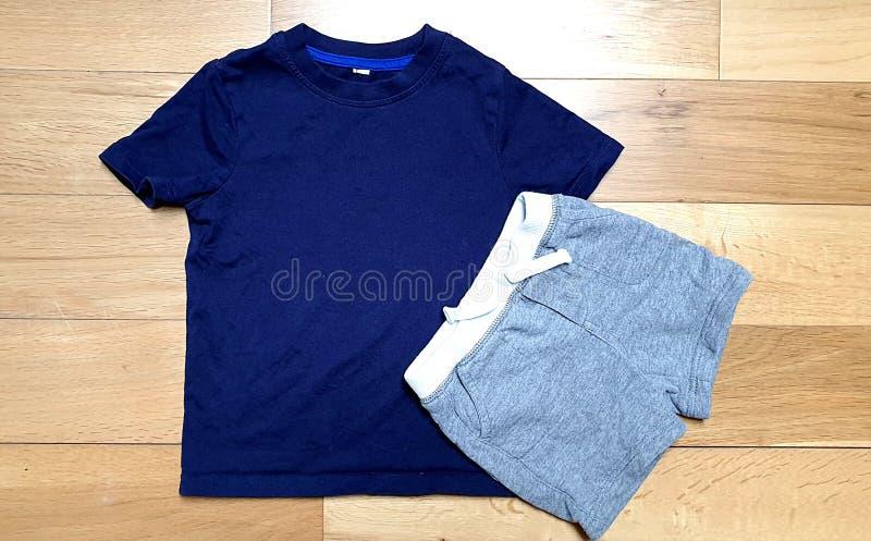 La photographie courante dénommée, le T-shirt bleu d'enfants et les shorts gris raillent sur le fond boisé clair images stock