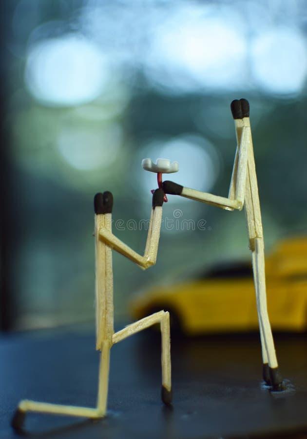 La photographie créative du garçon proposer à la fille avec la fleur utilisant des matchs collent photo stock