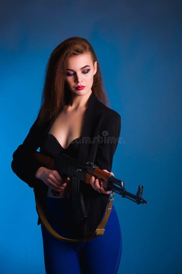 La photographie de mode de fille dans le studio avec une arme à feu est dangereuse images stock
