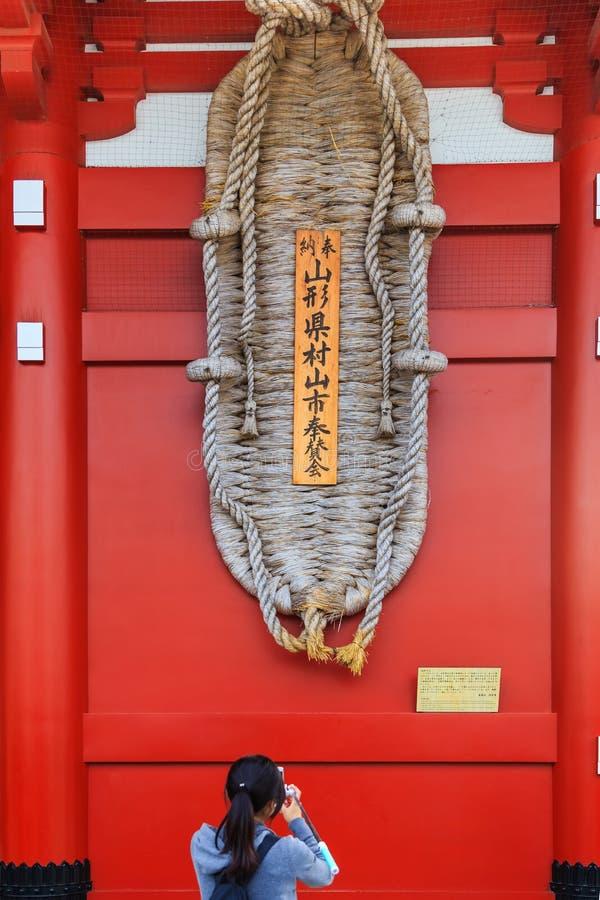 La photographie de prise de touristes non identifiée des sandales géantes d'owaraji accrochent à la porte de tonnerre du temple d photos stock