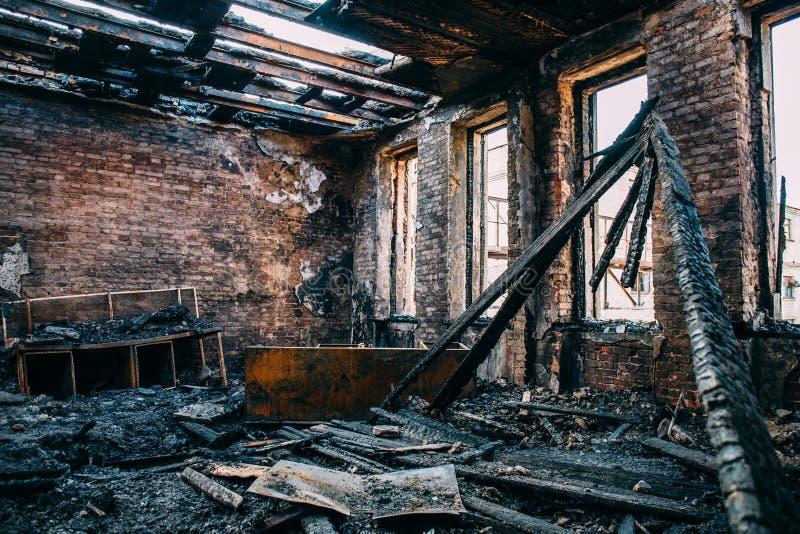 La pièce brûlée intérieure avec des murs, des meubles et le plancher en cendre et charbon, a ruiné le bâtiment après le feu images stock