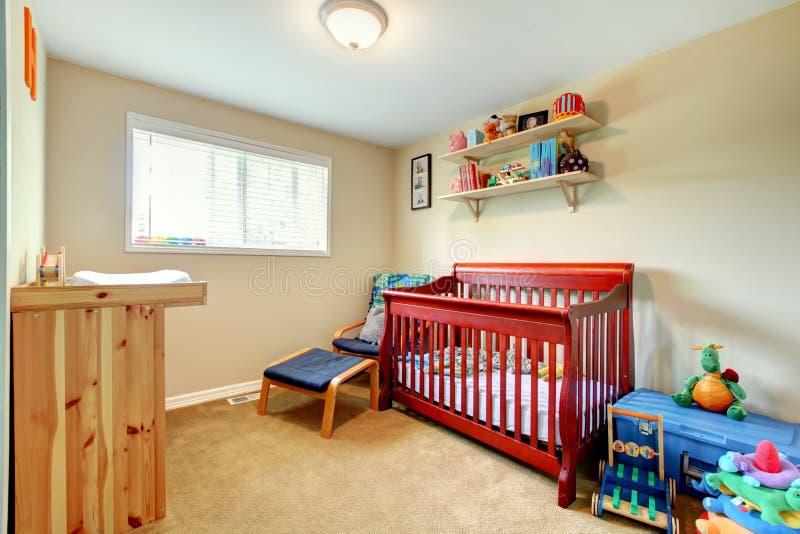 La pièce de bébé avec le rouge a souillé la huche en bois et l'intérieur lumineux images stock