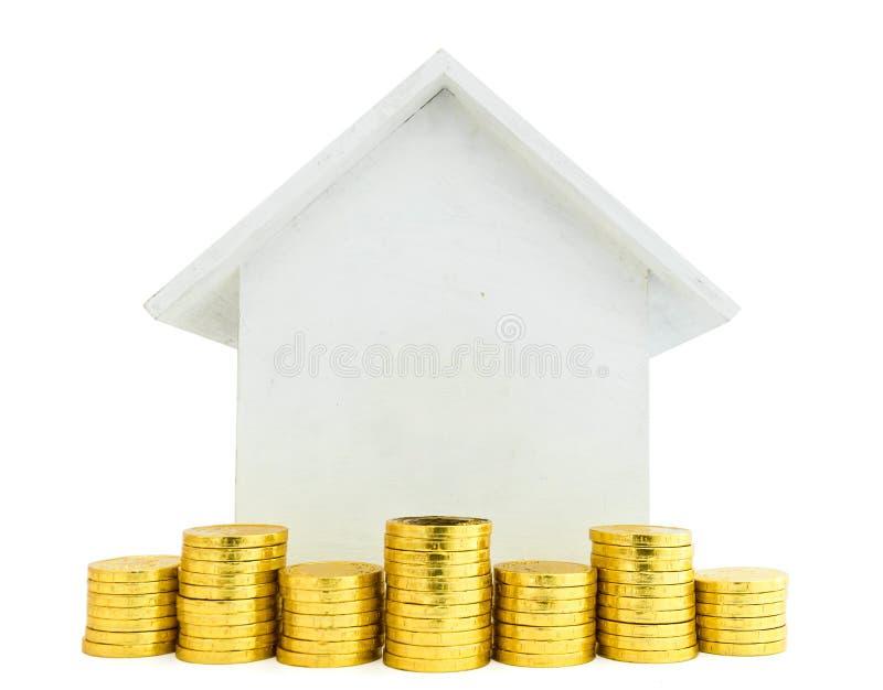 La pièce de monnaie d'or devant le modèle en bois de maison avec le blanc a isolé b photos stock