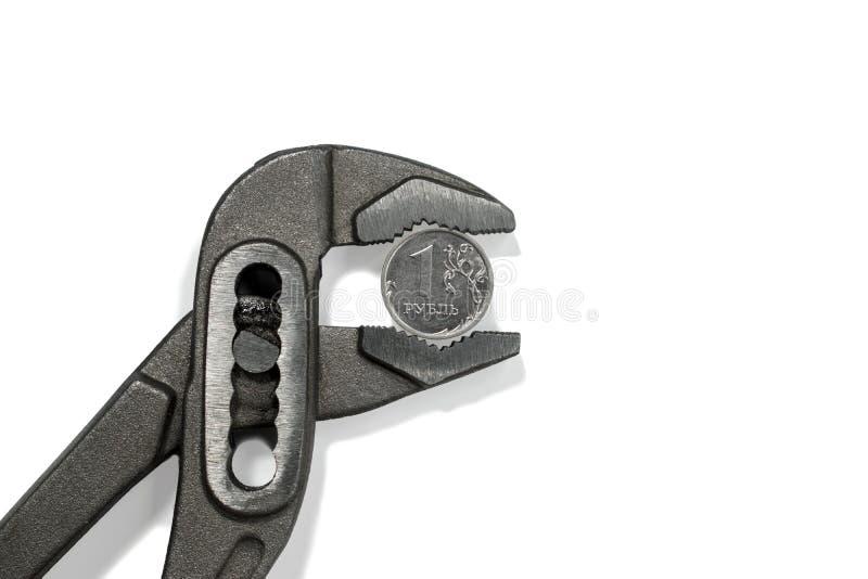 La pièce de monnaie dans l'étau sur le fond blanc photographie stock