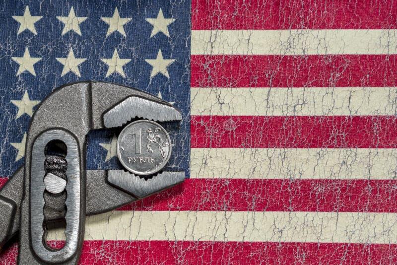 La pièce de monnaie dans l'étau sur le fond du drapeau criqué des Etats-Unis photo stock