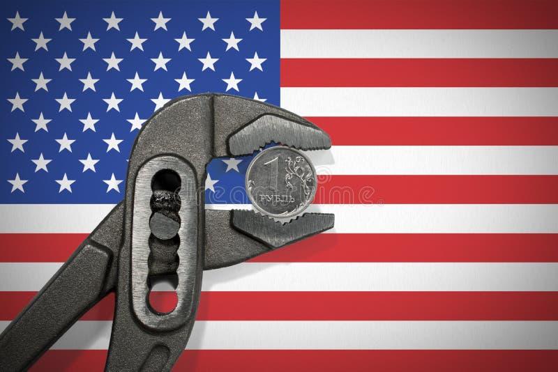 La pièce de monnaie dans l'étau sur le fond du drapeau des Etats-Unis photo stock