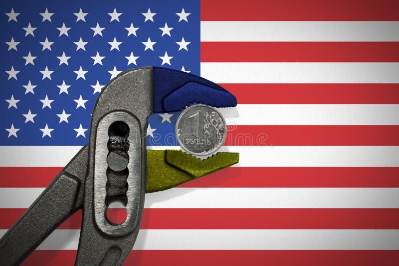 La pièce de monnaie dans l'étau sur le fond du drapeau des Etats-Unis image libre de droits
